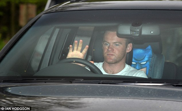 Drive time: A glum-looking Wayne Rooney arrives at Carrington in his car
