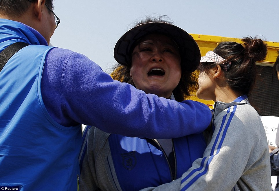 A family member of a missing passenger onboard the capsized Sewol ferry, cries as she shouts to government officials demanding faster and more efficient rescue work at the port where many family members wait for news
