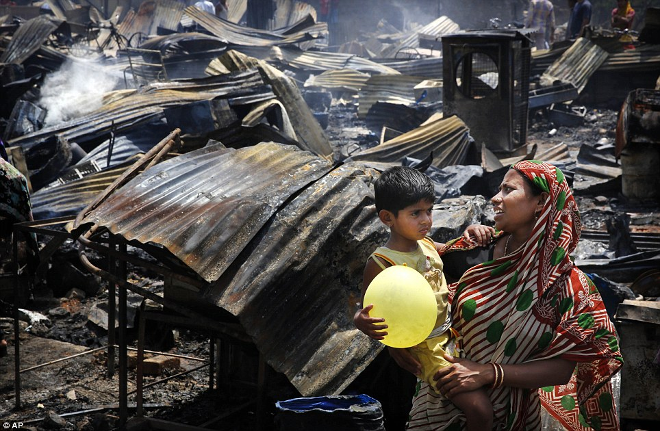 Woman and her son standing in front of burnt slum houses
