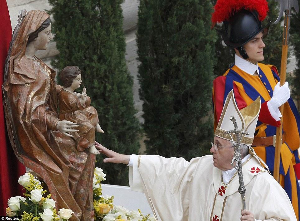 Respeitoso: Papa Francis toca a estátua da Virgem Maria, como ele chega para a cerimônia de canonização de Papas João XXIII e João Paulo II