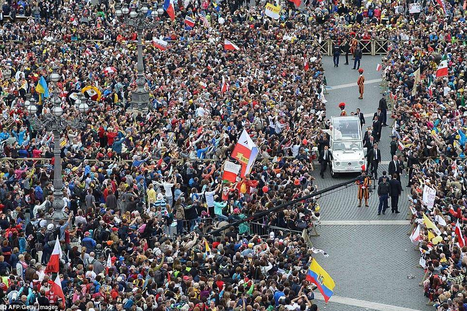 Todos tentando obter uma visão dele: Papa Francis cumprimenta a multidão de seu papamóvel após a missa de canonização de Papas João XXIII e João Paulo II