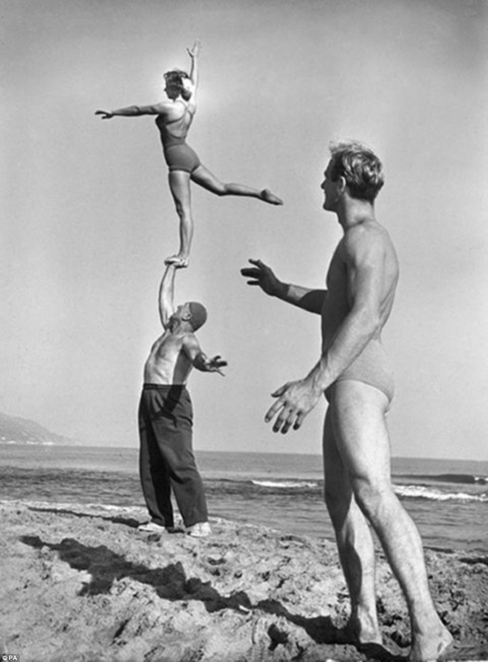 The images span three decades from the 1940s to 1960s, and include pictures of former U.S. president Harry Truman and James Bond star Roger Moore. This photograph shows a performers on Santa Monica beach