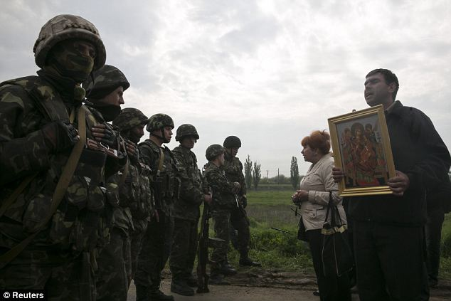 Desperate: Civilians plead with Ukrainian troops at a checkpoint as fighting raged just a few miles away