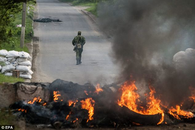 Defiant: An armed pro-Russian rebel walks behind a burning barricade on their checkpoint in Slaviansk