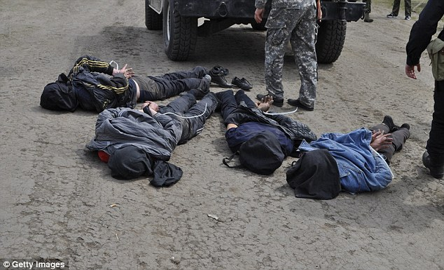Arrested: Ukrainian military arrest the four men believed responsible for shooting down two helicopters, killing one pilot and a serviceman in the resulting crash