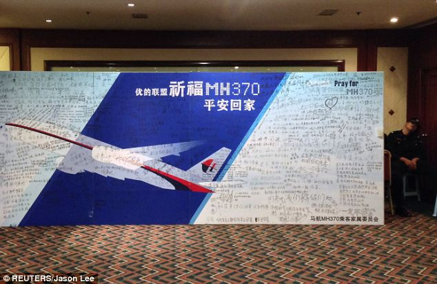 A policeman naps beside a board written with messages for passengers aboard the missing fight at the hotel