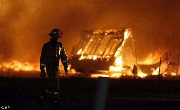 A firefighter walks past a burning mobile home at a mobile home park near Prairie Grove Rd and Douglas during Oklahoma wildfires in south Logan County