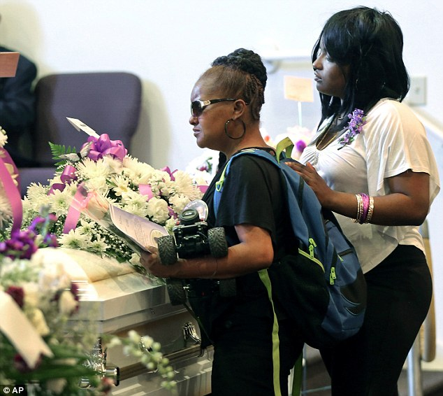 Saying goodbye too soon: Sharain Spruill, left, stands at the casket of  her son, 8-year-old Martin Cobb, holding his toy truck during her son's funeral at Mimms Funeral Home on Friday