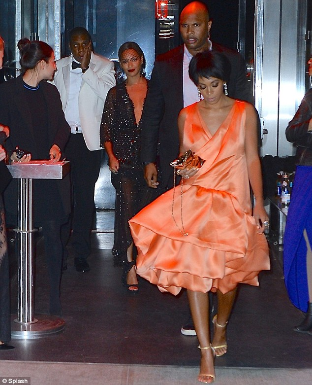 What happened here? Jay Z holds his face as Solange marches ahead angrily minutes  after attacking him in the elevator