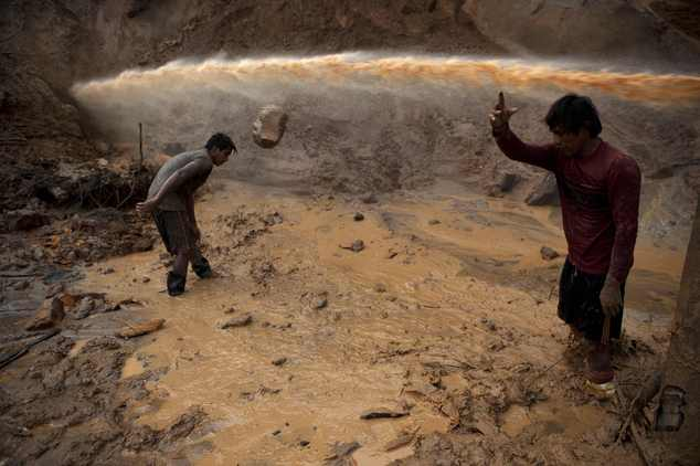 """In this May 3, 2014 photo, a jet stream of water passes above two miners known as """"Maraqueros"""" who remove stones and chunks of tree trunks that have been rel..."""
