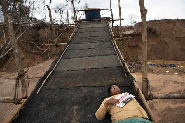 In this May 5, 2014 photo, a miner rests on top of a rustic sluice-like contraption layered with pieces of carpets to capture the gold deposits from water se...