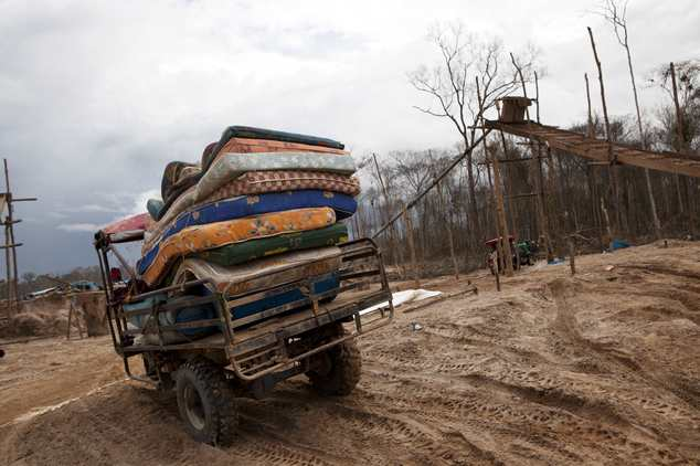 In this May 5, 2014 photo, a motortaxi delivers a cargo of mattresses to a mining camp in La Pampa in Peru's Madre de Dios region. An estimated 20,000 wildca...