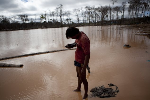 In this May 3, 2014 photo, a miner roughly estimates his handful of gold he mined, after working for over 24-hours,  in La Pampa in Peru's Madre de Dios regi...