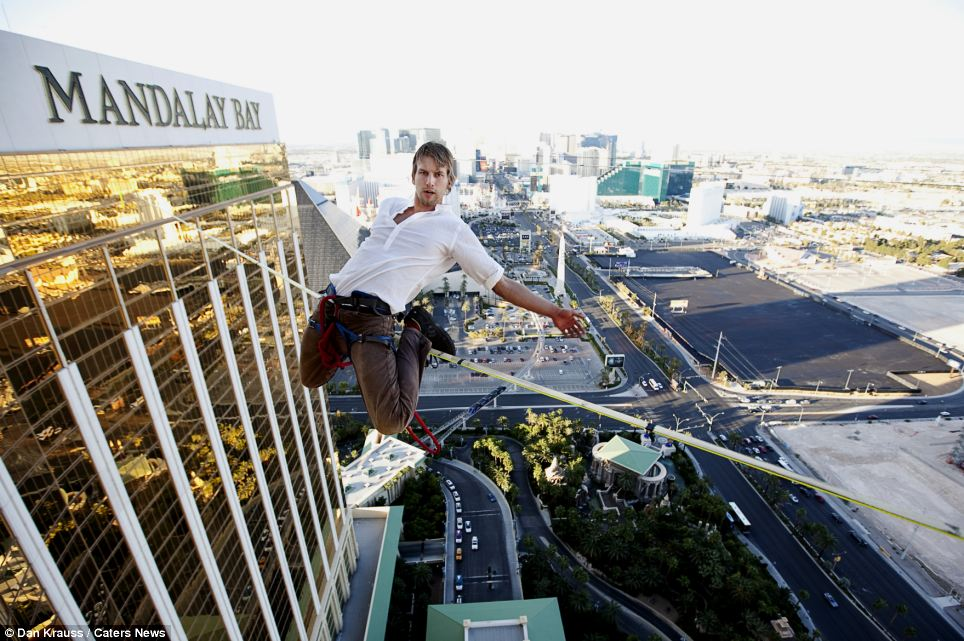 Meanwhile, another slackline expert Hayden Nickell hooks his feet over a line hundreds of feet above the ground in Las Vegas and poses for pictures as he performs a daredevil balancing trick with just a rope, clips and a harness as safety measures