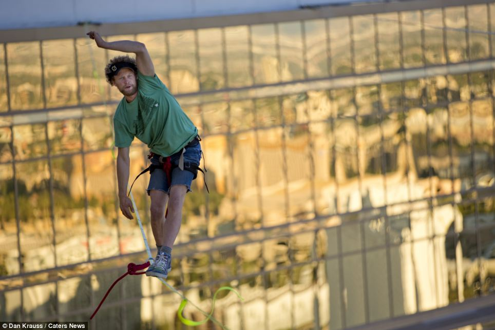 Easy does it: Andy Lewis pauses to correct his balance on another crossing. He eventually broke the world record for walking the longest distance on a slackline in an urban environment when he completed the task without falling on his third attempt