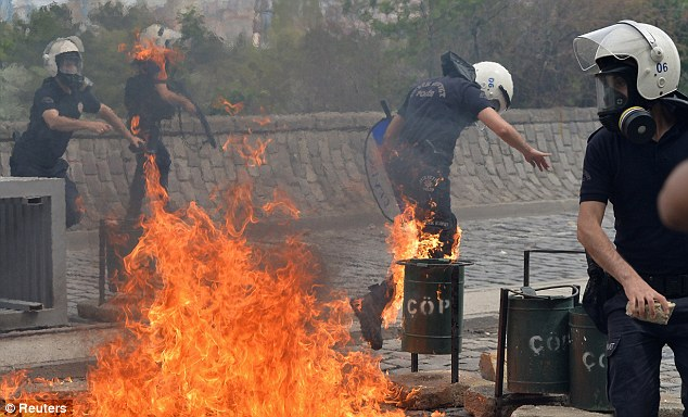 Street battle: Riot police run away from the flames of a fire bomb thrown by protesters as they demonstrate to blame the ruling AK Party government on the mining disaster