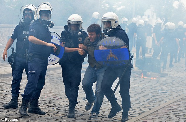 Arrest: Riot police detain a protester during a demonstration against the ruling AK Party