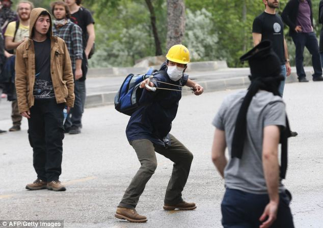 A protester catapults stones at Turkish police during a demonstration in Ankara