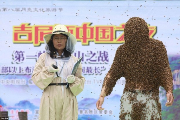 Winging it: Liangming was covered by approximately 100,000 bees during his amazing endurance test