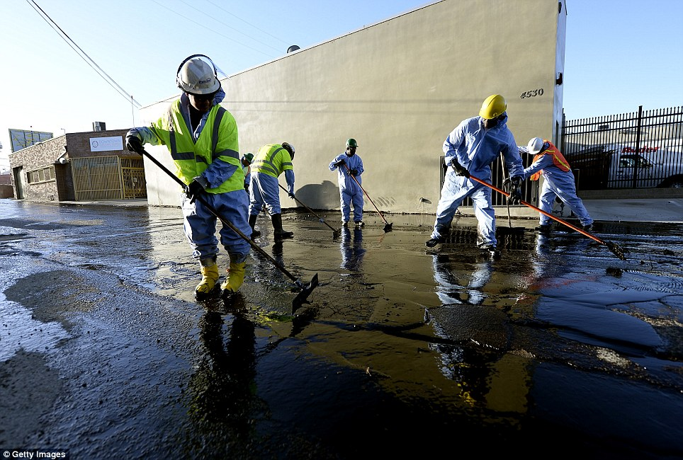 Clean up: Hazardous material specialists are also working at the scene amid concern that the massive spill could cause an environmental disaster. Fire Department spokesman Erik Scott says there is currently no 'visible evidence' that the oil has entered storm drains