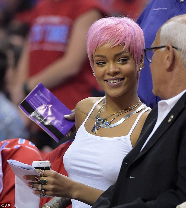 A new fan: Rihanna chatted to the gentleman beside her as she caught up on the action on the court