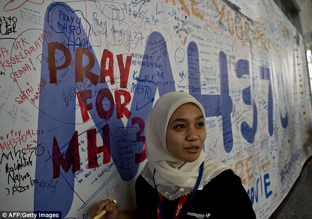 A Malaysia Airlines employee writes a message expressing prayers and well-wishes for passengers of MH370 at the Kuala Lumpur International Airport mosque