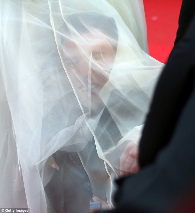Bizarre: The journalist put his head under America's dress much to her bemusement
