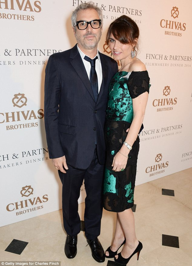 Getting cosy: Sheherazade Goldsmith cuddled up to her partner Alfonso Cuaron at the bash