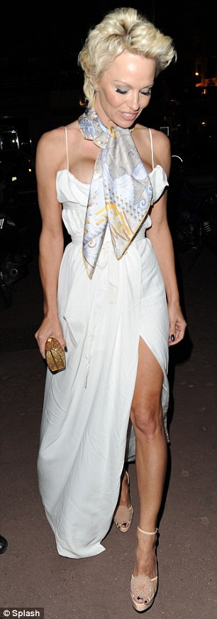 Putting her best foot forward: The former actress covered her chest with her patterned silk scarf but exposed her toned legs in the wrap dress as she made her way onto the yacht upon which the cocktail party and backgammon tournament was being held
