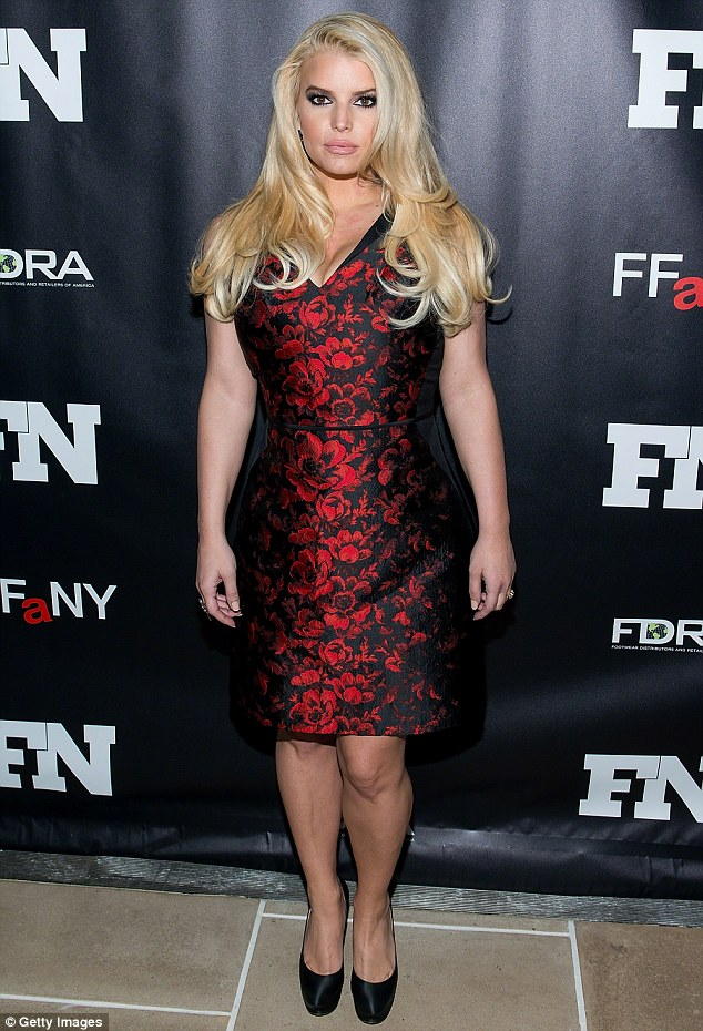 Getting there: Jessica pictured at an event in New York in  December last she had already lost enough weight to carry off this figure hugging dress