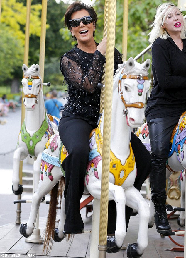 Horsing around: Kris Jenner was beaming on a merry-go ride in Paris on Monday... but is fuming about Kylie's hair