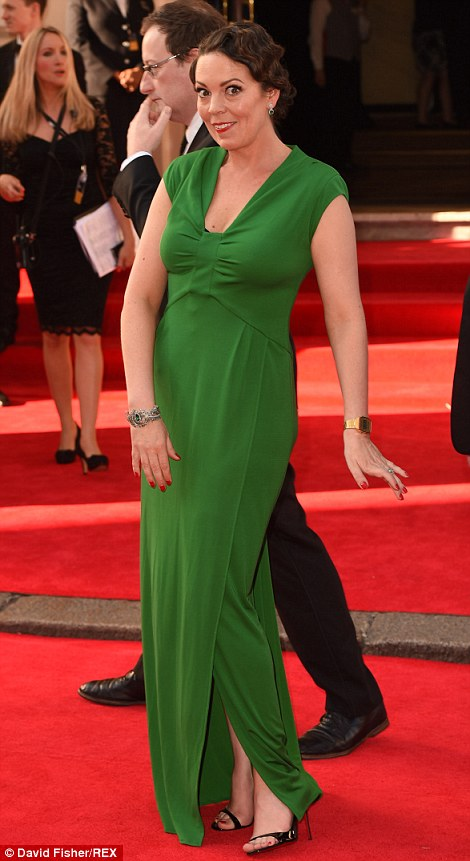 Green with envy: Olivia wore a simple floor-length gown and her short hair in retro waves