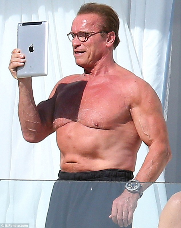 Spec-tacular: Bespectacled Arnold Schwarzenegger flaunted his chest as he took a selfie in Cannes on Sunday