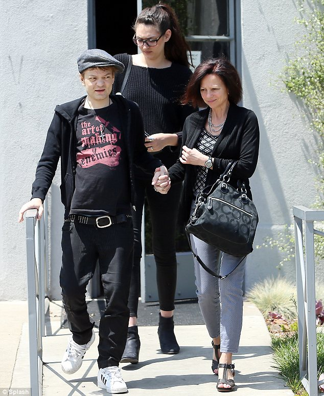 Almost unrecognisable: The frail Sum 41 frontman was supported by his fiancee (C) and another woman