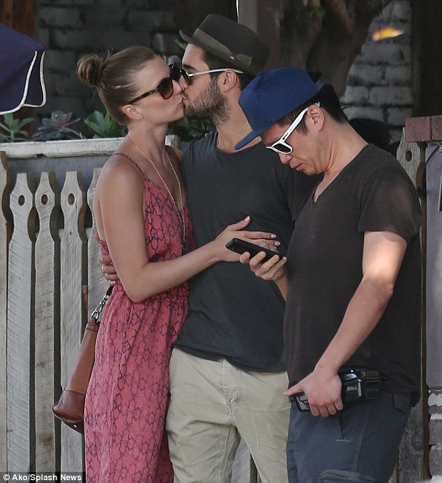 He's still not looking: The 26-year-old Brit pulled the blonde beauty in tight as their pal resolutely checked out his smart phone