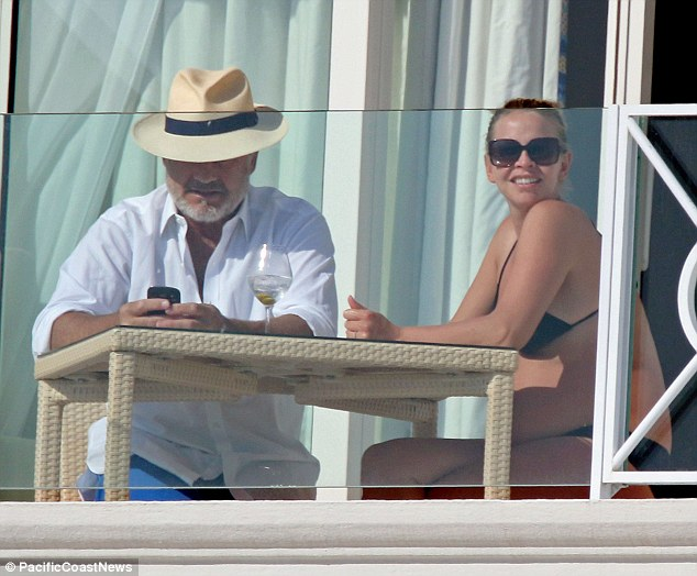 Daytime dapper don: While his wife soaked up the sun's ray, Kelsey covered up wearing a white shirt, blue shorts and a straw fedora
