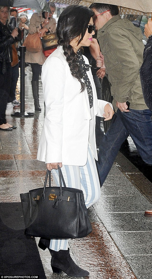 Stylish pair: Kourtney also opted for white and stripes as she rocked a white blazer over a pussybow blouse and striped trousers