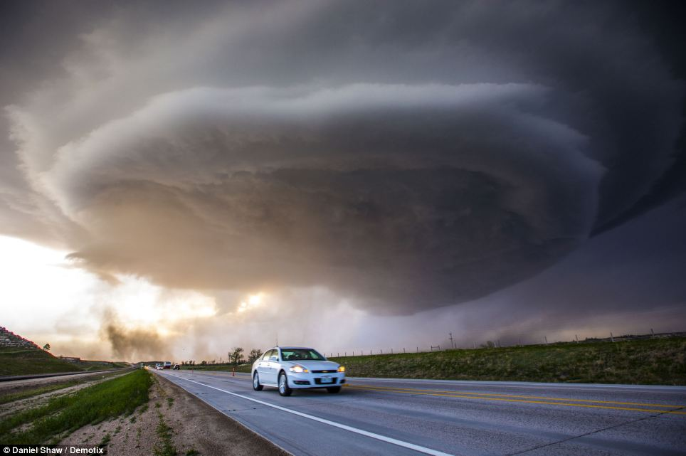 Terrifying: The giant thunderstorm appears as if it could swallow this car whole as it was captured while travelling across the High Plains