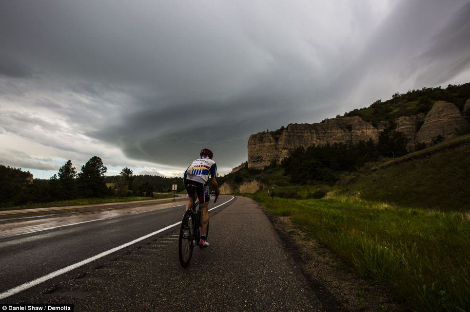 Brave: Despite the storm clouds gathering in the distance, a brave cyclist refuses to be put off from his journey