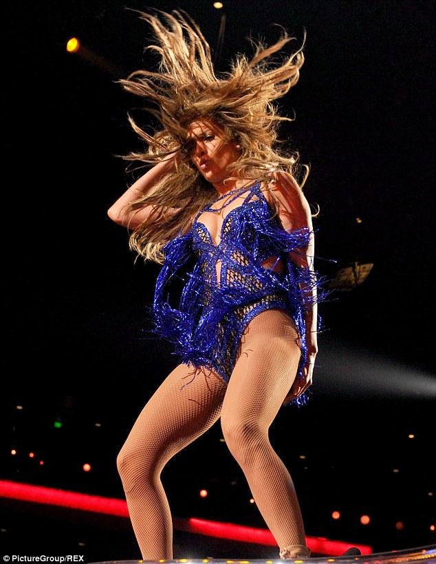 Hair's how: The singer ran her hand through her golden locks as she performed her signature hair flips