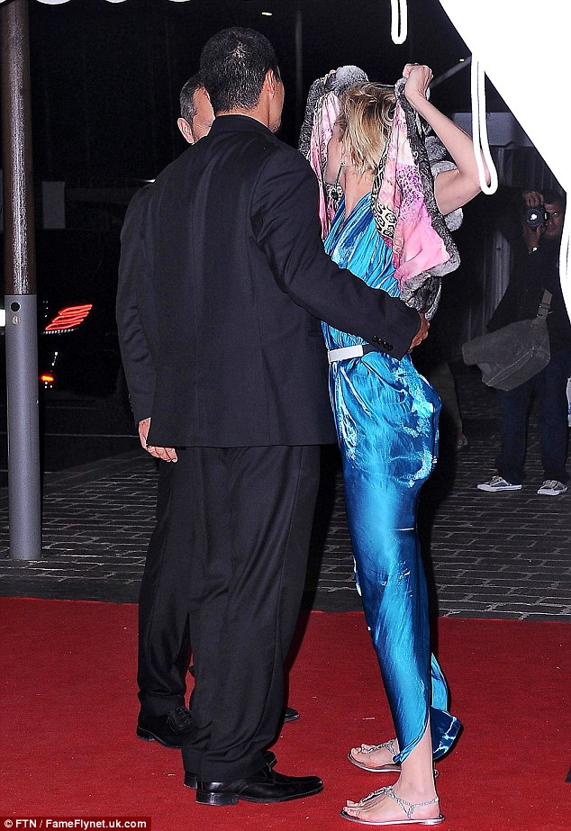 Glam gal: The blonde bombshell looked carefree in her bright blue gown, diamonds, and luxurious short-sleeved mink coat