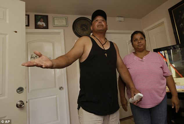 'He does his best to do whatever she wants': Neighbors Enrique Rios, left, and wife, Lourdes Hernandez express their disbelieve on the charges against their neighbor, Isidro Garci in Bell Gardens, California. Meanwhile, police maintain she was brainwashed all along