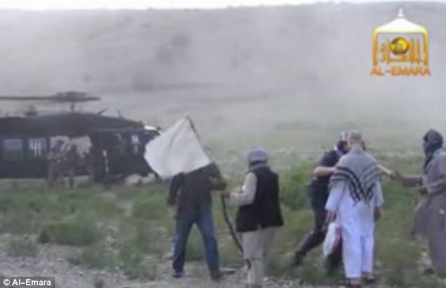 Trade: As one of the helicopters lands, Bergdahl is led to his rescuers by the two men. The video captures both sides quickly shaking hands (seen right) as Bergdahl looks on