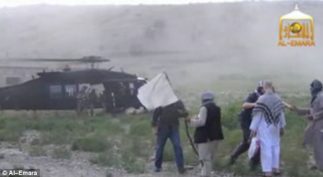 As one of the helicopters lands, Bergdahl is led to his rescuers by two men, one leading him by the hand and another waving a white cloth tied to a wooden stick
