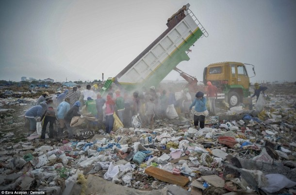 The recycling pickers cover their mouths as dust from the truck spreads across the site