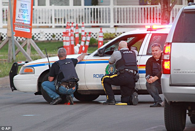 Duck and cover: Police officers take cover behind their vehicles in Moncton