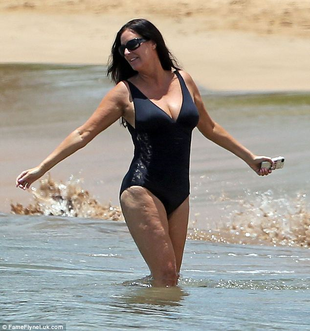Stunning: The TV star showed off her enviable curves in a plunging black swimsuit