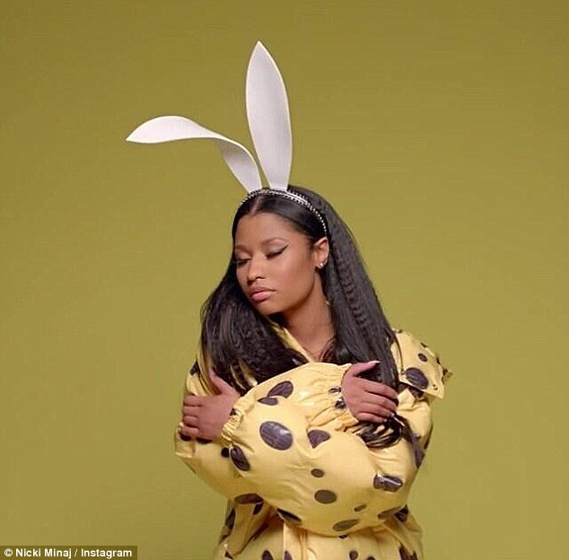 Playful: Nicki then wears a yellow raincoat sporting brown polka dots and dons bunny ears