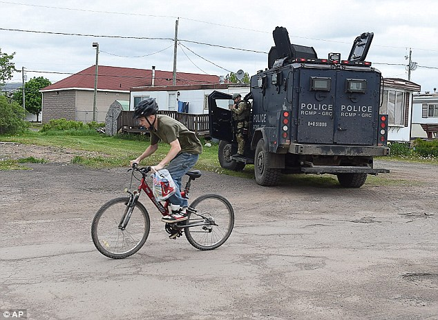 Life as usual: A teen rides his bike past a trailer where murder suspect 24-year-old Justin Bourque resides in Moncton, with an armored police vehicle parked out front
