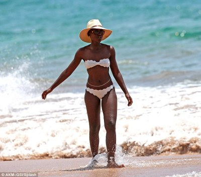 Star quality: Lupita looked the height of style as she stood against the blue water